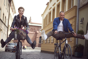 Two of friends riding bicycles in city
