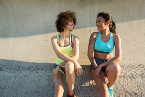 Two smiling healthy women in sportswear talking while having a break during work out outdoors