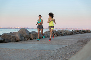 Two smiling pretty fitness women running together along the beach