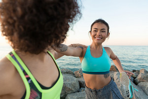 Two smiling young fitness women warming up before jogging outdoors