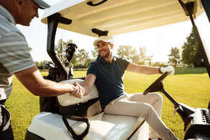Two sportsmen shaking hands on a golf course