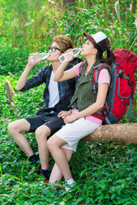 Two tourists sitting and drinking water