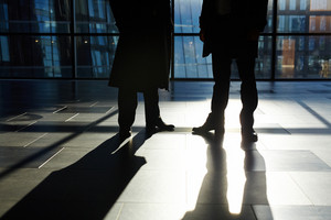 Two unrecognizable white collar workers standing against panoramic window in modern office lobby, their shadows reflecting on tile flooring