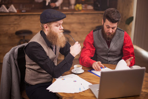 Two young bearded entrepreneurs running their business from a coffee shop. Successful men. Talking about fianance and econmy.