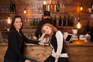 Two young beautiful women talking in the pub. Having fun in a hipster pub.