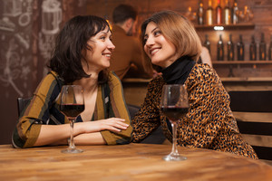 Two young female best friends relaxing with a glass of wine in a restaurant. Celebrating friendship.