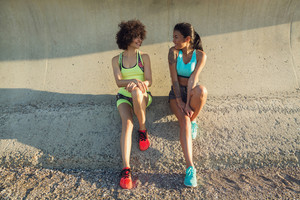 Two young fitness women in sportswear talking while having a break during work out outdoors