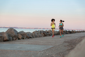 Two young sportswomen running together and talking outdoors