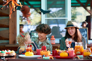 Two young woman and little boy enjoying Halloween dinner outdoors