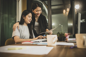 two younger asian woman freelance discussing to job on office computer