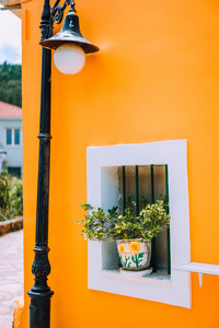 Typical Greek architecture details concept. Orange house wall, flowers in the pots, lantern, traditional house in Greece