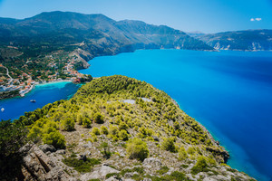 Ultra wide shot of Assos village in morning light, Kefalonia. Greece. Beautiful turquoise colored bay lagoon water surrounded by pine and cypress trees along the coastline