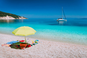 Umbrella and beach accessories on pebble beach on lazy summer day. Sailing boat stays at anchor in calm crystal clear blue sea water