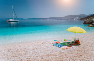 Umbrella and beach accessories on pebble beach on lazy summer day under bright sun light. Sailing boat stays at anchor in calm crystal clear blue sea water