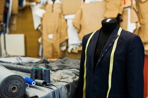 Unfinished jacket on dummy and sewing accessories in tailoring shop