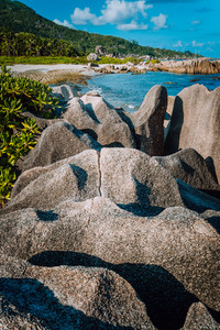Unique big granite rocks in lush green foliage on hidden picturesque tropical coastline. Grand L Anse, La Digue, Seychelles