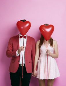 Unrecognizable couple with balloon holding hands
