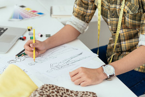 Unrecognizable fashion designer drawing sketches in his workshop