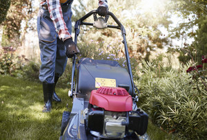 Unrecognizable gardener turning on mower