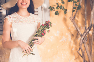 Unrecognizable happy woman with bouquet of flowers standing next to wall