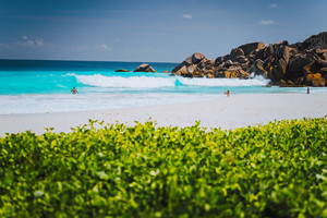 Unrecognizable tourist dabble in blue colored waves at Grand Anse beach, La Digue Island, Seychelles