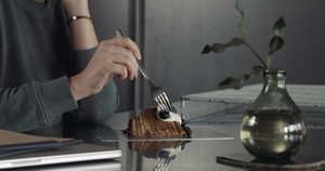 unrecognizible woman take a slice of cake and ut fork then
