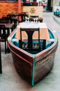 Unusual restaurant interior: dining table in the colorful fish boat. Marine ambience