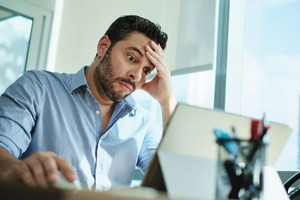 Upset business man working with laptop computer in office, feeling stressed and anxious for possible data loss. Adult Hispanic executive under stress at work for technology problems and software pc