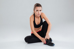 Upset fitness woman with pain in her leg sitting on the floor over gray background