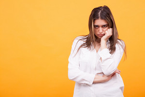 Upset young girl wearing white shirt over yellow background. Facial expression