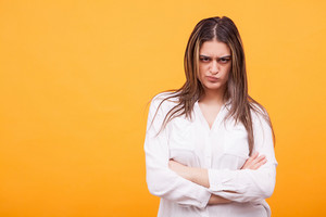 Upset young woman casualy dressed standing over yellow background. Facial expression
