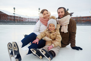Urban family on skates sitting on ice of rink