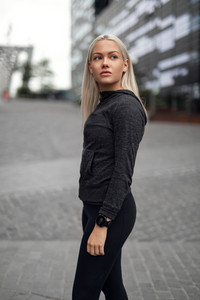 Urban scandinavian woman in workout outfit standing in the city