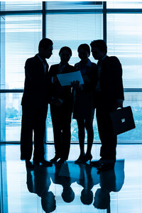 Vertical image of a blurry business team discussing the strategy