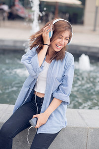Vertical image of a cheerful young girl listening to the music with her earphones outside