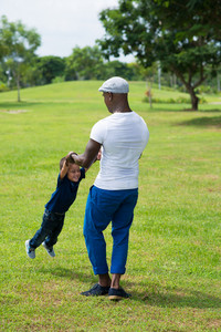 Vertical image of a father carrying his little son in the park on the lawn