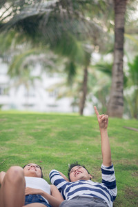 Vertical image of a happy young couple lying on the grass, a boyfriend pointing at something