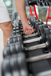 Vertical image of a male athlete taking a dumbbell from a row