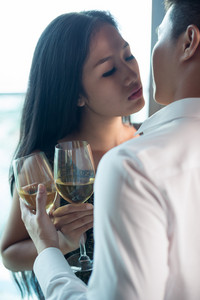 Vertical image of a sensual couple holding glasses of wine