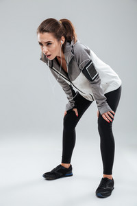 Vertical image of a tired female runner in studio over gray background