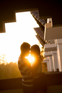 Vertical image of a young couple kissing at sunset
