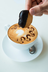 Vertical image of an espresso cup and a human hand holding a tasty chocolate snack