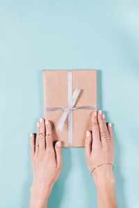 Vertical image of female hands holding a box with gift on a blue background