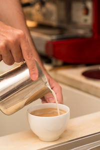 Vertical image of human hands pouring milk in the coffee on the foreground