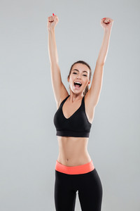 Vertical image of screaming fitness woman with hands overhead over gray background