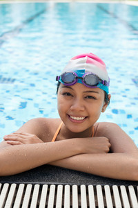 Vertical portrait of a young female swimmer smiling and looking at camera