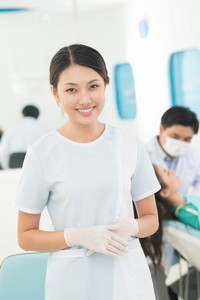 Vertical portrait of a young medical worker assisting at dentistry