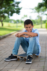 Vertical portrait of young mulatto guy sitting on the skateboard in the park