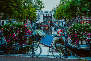 Vibrant flowers and bicycle bike on a bridge of Amsterdam at early evening. Twilight on the famous UNESCO world heritage canals of Amsterdam, The Netherlands