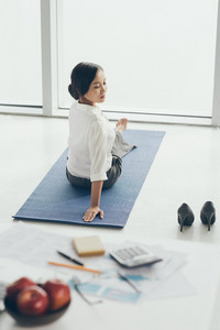 Vietnamese business woman practicing yoga before work